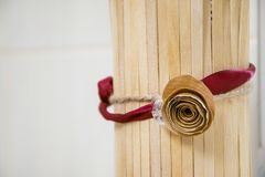 Beautiful handicraft rose with satin ribbon. Focus on nice paper blossom with decorative burgundy string and rope on wooden tube. Creative handmade design stock photo