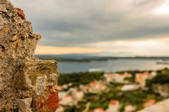Focus on an old rock with Paklinski Island in blurry background in Hvar, Croatia royalty free stock photo