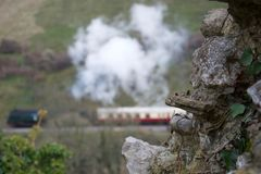 Focus on old stone wall; traditional steam train and carriages in background stock images