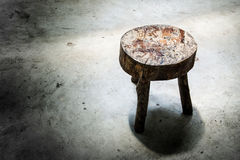 Focus old wooden stool on the cement floor on the light Royalty Free Stock Image