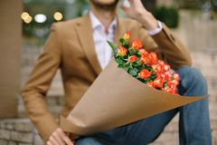 Focus On Bunch Of Roses, Folded In Craft Paper Holded By Man Royalty Free Stock Photo