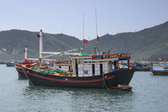 Focus on one fishing boat among many moored in front of village Stock Photo