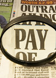 Focus on PAY !. A closeup image of the word pay in a newspaper headline viewed through a magnifier. Pay is the subject of government policies in many countries Stock Photos