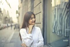 Focus Photo of Woman in White Long-sleeved Dress Standing at the Front of Gray Building Royalty Free Stock Photo