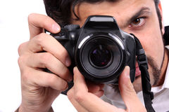 Focus of a Photographer. A closeup view of an Indian photographer focussing his camera, on white studio background Royalty Free Stock Images
