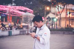 Focus Photography of Man Wearing White Sports Shirt Holding Smartphone Near Buntings Royalty Free Stock Photo