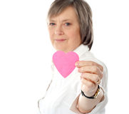 Focus on pink paper heart. Aged woman holding it Stock Images