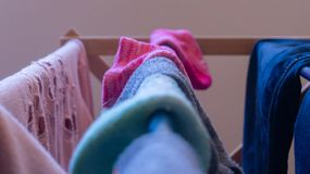 Focus on a pink sock drying on a laundry rack with other woman`s clothes, and mismatched socks blurred in the foreground. stock photos