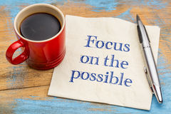 Focus on the possible. Motivational handwriting on a napkin with a cup of coffee Royalty Free Stock Photos
