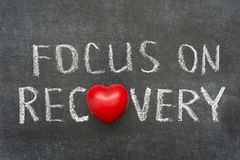 Focus on recovery. Phrase handwritten on blackboard with heart symbol instead of O Stock Photos