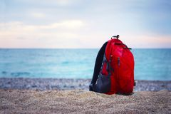 Red backpack for traveling stands on a sandy sea shore on the ba. In focus red backpack for traveling stands on a sandy sea shore on the background of blurred Royalty Free Stock Image