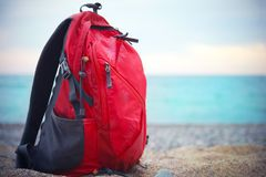 In focus red backpack for traveling stands on a sandy sea shore. On the background of blurred sea Royalty Free Stock Photos
