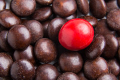 Focus on red chocolate candy against heaps of brown candies Royalty Free Stock Photo