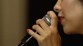 Woman with red lips sings in microphone stock footage