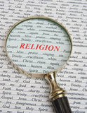 Focus on religion. A closeup image of the word 'Religion' in bold red text with a magnifier to emphasize the subject. The background includes many topics of Royalty Free Stock Image