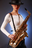 Focus on sax. Sexy young woman with saxophone (focus on sax Royalty Free Stock Photo