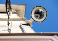 Focus on security CCTV camera or surveillance system. On building oin a city stock photography