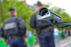 Security CCTV camera or surveillance system with police officers on blurry background. Focus on security CCTV camera or surveillance system with police officers royalty free stock image