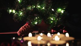 Focus shift from candles in the front to lights in the back. Christmas decoration on dark background with candles in front and lights on green in the back stock video
