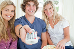 Focus shot on three friends as they use the remote  Royalty Free Stock Photos