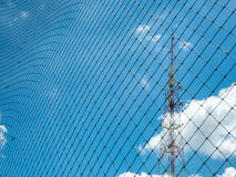 Focus Signal tower behind the plastic nylon net. Under the blue sky and cloud background Royalty Free Stock Image