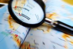 Singapore. Our little red dot - A photograph showing the small city state of Singapore being focused upon by a magnifying glass held at the world atlas map Stock Photography
