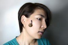 Snail massage on face of asian woman Stock Photos