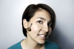 Snail massage on face of asian woman Stock Photography