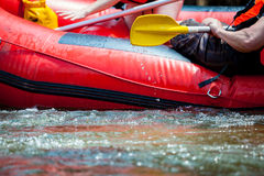 Focus some part of young person are rafting in river. Royalty Free Stock Image