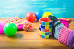 Focus Spot women`s hands, gloves, Silk hat, colored balls and a cup of coffee on wood table. Royalty Free Stock Photos