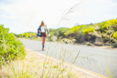 Focus on straw with blonde walking on the road on background Stock Images