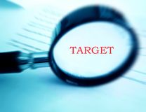Focus on target. Right on target - A magnifying glass used focused on the word target in bold and red color.  Conceptual image for focusing on the aim and target Stock Photo