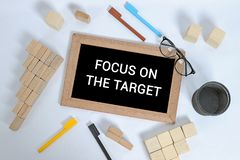 FOCUS ON THE TARGET text on blackboard with office accessories. Business motivation, inspiration concepts, pen and pencil case, royalty free stock images