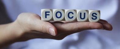 Focus. On the task at hand. Cube letters main clarity of photo on palm Stock Images