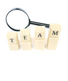 Focus on team. A conceptual photograph with the word team spelt out in blocks, taken with a magnifier glass.  Team building and team working concept. White Stock Photos
