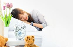 Focus to alarm clock with blur focus of woman stock images