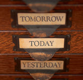 Focus On Today. Stack of three old, oak flat file drawers with Yesterday, Today, and Tomorrow printed on tags in tarnished brass label holders. Shallow DOF with Royalty Free Stock Photo