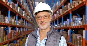 Focus on warehouse worker smiling to the camera