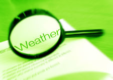 Focus on weather. A concept photograph image of a magnifier focused on the word weather. Simple monochrome green image with copy space.  Conceptual image for Royalty Free Stock Photography
