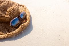 Focus on Weave hat and sunglasses on white sand beach. - You can stock images