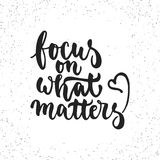Focus on what matters - hand drawn lettering phrase isolated on the white grunge background. Fun brush ink inscription Royalty Free Stock Images