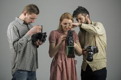 Focus on what matters. Paparazzi or photojournalists with vintage old cameras. Group of photographers with retro cameras. Retro style women and men hold analog royalty free stock image