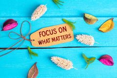 Focus on what matters text on paper tag. With rope and color dried flowers around on blue wooden background stock photography
