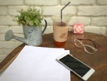 Focus on white paper for placing letters.Ice tea in plastic glasses, glasses,smartphones and documents on the wood table next to t Royalty Free Stock Photos