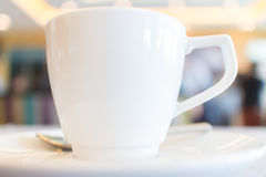 Focus on white tea cup with blurred background of conference bre Stock Image