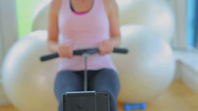 Focus on a woman rowing in a machine Stock Photo