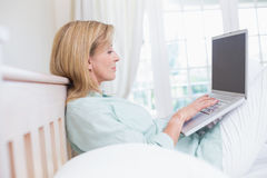 Focus woman using laptop in her bed Royalty Free Stock Images