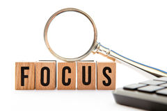 Focus. Wooden block letters with magnifying glass and keyboard Royalty Free Stock Images