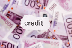 Focus on the word CREDIT on piece of torn white paper with blur Royalty Free Stock Photography