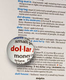 Focus on word dollar. On dictionary page by a glass globe magnifying to zoom and highlight Royalty Free Stock Photography